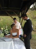 Hannah sits on a bench in a wooden shelter to sign the wedding register, Lee is standing behind her.