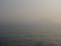 A conical mountain is just visible through mist across the sea