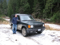 Dugly stands in front of a mud spattered Land Rover Discovery.  Snow lies on the ground and there are trees all around.