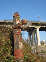A carved wooden totem pole with outstretched arms stands in front of a high concrete bridge.