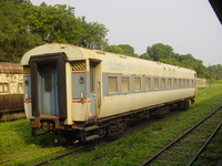 A railway carriage with 'SLEEPING CAR' painted on the side at the near end and '1ST' at the far end.