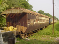 A rusty and collapsing railway carriage with wooden shutters on the windows and an open-platform at each end.