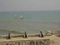 Cannons pointing out to sea from castle battlements towards fishing boats with patchwork sails.