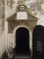 The entrance to a dark cell with a thick wooden door.  A skull and cross bones are carved above the doorway.