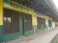 Railway station platform building painted green and yellow, over the doors and windows are two signs 'Cafeteria' and 'Travellers Fare'.  Between two windows is a painted logo and 'Railway Catering Service'.
