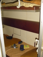 A railway sleeper cabin with two folding bunk beds.  Each bunk with a sheet, pillow and blanket.