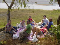 Group of people having a picnic on a rock by a reservoir