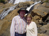 Parents standing in front of a rocky waterfall