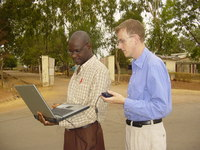 Two people measuring wireless signal strength with a laptop, standing on a dusty road in front of a gate