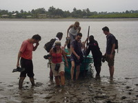 A boatload of people climb out into deep mud