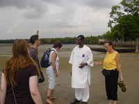 A small group of people meet a local man dressed in s shining white outfit