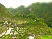 Small houses with thatch or metal roofs among rice terraces in the mountains.