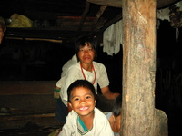 A woman and young boy in a wooden house.