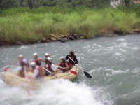 Six people and a guide in a rubber raft paddling through rapids.