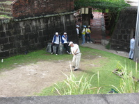 Golfers playing between old stone walls.