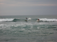 Two surfers surfing.