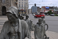 Metal statues of pedestrians walking towards a road, descending through the pavement and emerging on the other side.