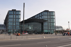 A modern building of metal and glass seen across a plaza, a sign on the front reads 'Berlin Hauptbahnhof'