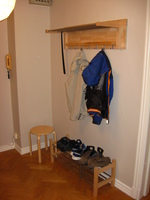 A wood and metal coat rack with a couple of coats hanging from it, attached to a large wooden board and the wall.  Below is a shoe rack.