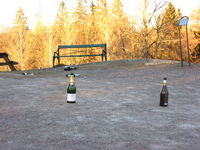 Champagne bottles and other rubbish litter the rocky ground.