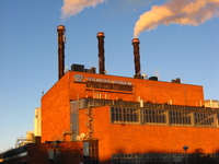 A large industrial building in red brick, glowing in the low winter sun.  Two of the three chimneys are giving off steam.
