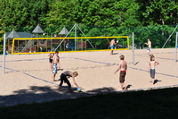 Young people playing volleyball on a sand court in bright sunshine.