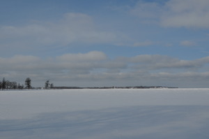 A white surface stretches out into the distance.  On the left a promontory reaches out into the lake.