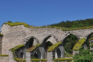 A ruined church, stone arches against a vivid blue sky.  A tree-covered hill in the backgroun.