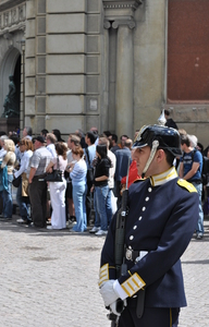 A soldier in ceremonial uniform (complete with spiked helmet) stands guard in front of a crowd of tourists.