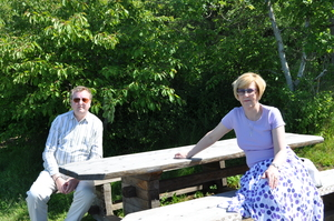 Parents sitting at a picnic table in the sunshine.