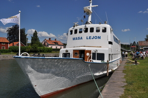 A white tour boat moored at one side of a canal.