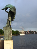 On the left, in the foreground, a bronze statue of a winged man marks the start of a bridge.  To the right, in the distance, a white-painted tall ship glows in the evening sun.