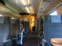 The interior of a first-class railway carriage, decorated in muted colours and wood panelling.