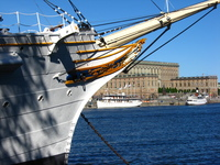 The bowsprit of a white sailing ship frames the Royal Palace.