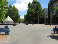 A pedestrian street with trees, benches and a fountain but few people.