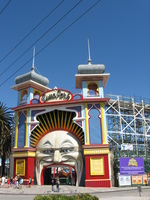 The colourful entrance to an amusement park, through the gaping mouth of a slightly sinister looking man in the moon.