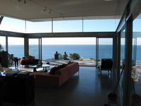 View from inside a largely glass building, furnished in a modern style.  Outside is a wooden desk with some people sitting on it, then the sea and sky.