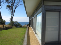 View along the side of a modern glass and steel house by the sea.