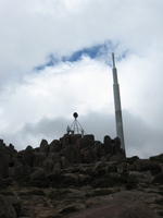 The peak of a mountain, a large communications mast rises behind it.