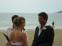 Hannah and Lee standing on the beach in front of the wedding celebrant.
