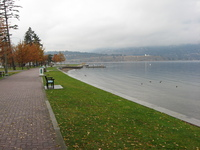 On the left a path stretches off, dotted with benches.  On the right a view across a lake to mountains on the far side.