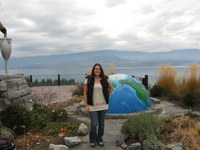 Tammie standing in front of a large globe, half-sunk into the ground. Behind her is a lake and mountains.