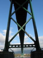 A green-painted suspension bridge is directly overhead going from top to bottom of the picture.  The bridge is seen between the spars of one of its towers.