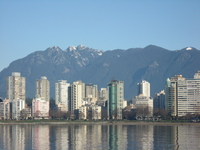 Across an expanse of water stand a crowd of tall apartment blocks, in the background mountains tower over them.