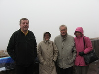Four cold-looking people huddle on an open terrace, in the background is a white sky.