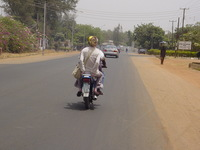 Eleanor clinging to the back of a motorbike, on a quiet road in Kaduna
