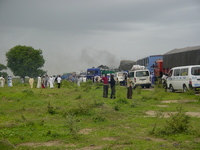 A queue of vehicles parked all over the road, people standing around. Black smoke rising in the background.