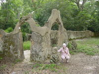 Eleanor squatting beside a sculpture at the entrance to the Osun shrine