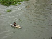 A muddy river with lumps of vegetation floating downstream.  On a dodgy-looking raft sits a small boy, paddling with flip-flops on his hands.