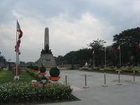 A tall monument in a park, surrounded by Philippines flags.